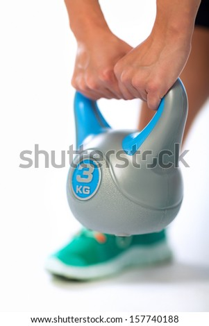 Fitness woman doing swing exercise with a kettlebell - stock photo