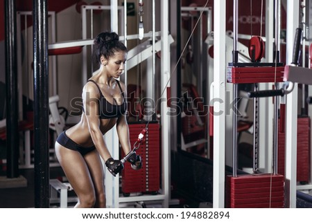 fitness woman doing triceps exercises in the gym. Brunette fitness girl in black sport wear with perfect body in gym exercising  - stock photo