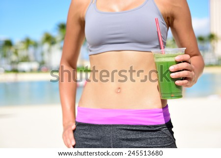 Fitness woman drinking green vegetable smoothie after running exercise.  Close up of smoothie and stomach. Healthy lifestyle concept with fit female model outside on beach. - stock photo