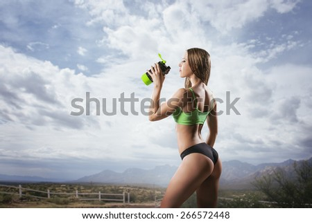 Fitness woman drinking water after running at outdoor Thirsty sport runner resting taking a break with water bottle drink outside after training. Beautiful fit sporty caucasian girl.  - stock photo