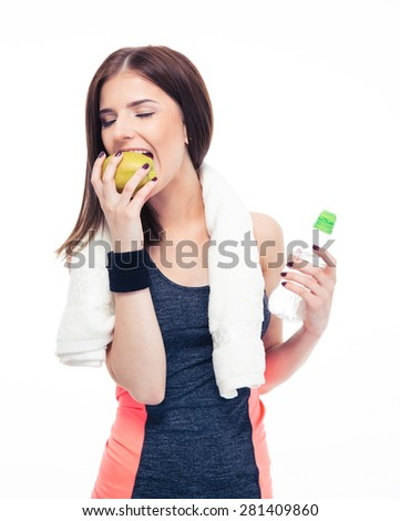 Fitness woman eating apple and holding bottle with water isolated on a white background - stock photo