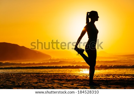 Fitness woman exercising and stretching legs on beautiful summer sunset or morning at beach. Female runner warming up or cool down. - stock photo