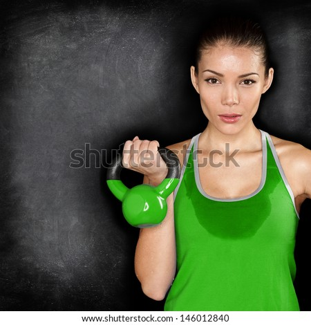 Fitness woman exercising crossfit holding kettlebell strength training biceps. Beautiful sweaty fitness instructor on blackoard background looking intense at camera. Asian Caucasian female model. - stock photo
