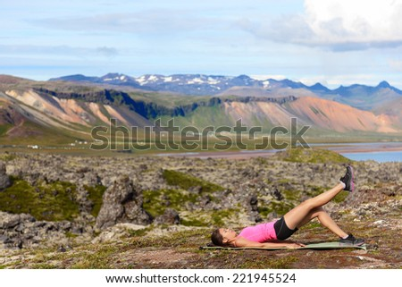 Fitness woman exercising single leg glute bridge exercise training butt and legs outside in beautiful nature landscape on Iceland. Fit female sports model working out. - stock photo