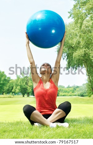 Fitness woman exercising with ball outdoors.