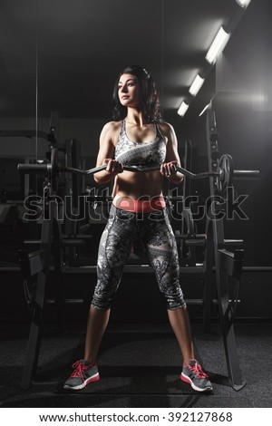 Fitness woman exercising with barbell in gym. Fitness woman deadlift barbell in the gym. Fitness woman in the gym. Sports and fitness - concept of healthy lifestyle. Crossfit woman. Crossfit stile - stock photo