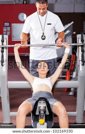 fitness woman exercising with barbell with help of her personal trainer in gym - stock photo