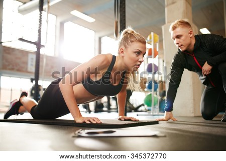 Fitness woman exercising with fitness trainer in gym. Woman doing push ups exercise with her personal trainer at health club. - stock photo