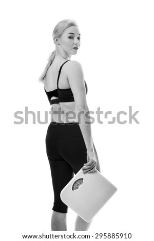 fitness woman holding scales looking happy - stock photo