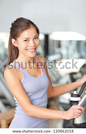 Fitness woman in gym training and working out on moonwalker gym equipment. Beautiful young multiracial Asian Chinese / Caucasian female model.
