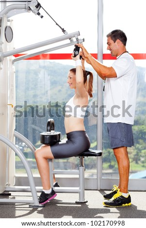 fitness woman in gym with personal trainer - stock photo