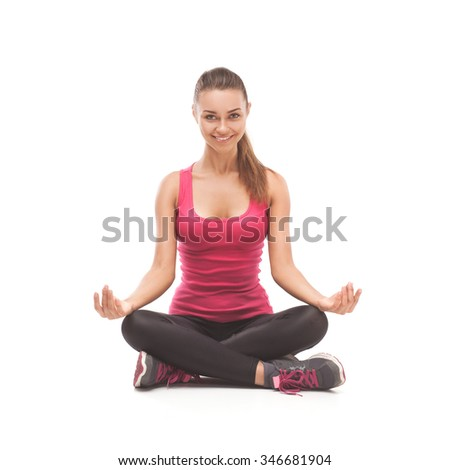 Fitness woman in pink shirt and black pants doing stretching exercise - isolated over white - stock photo