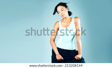 Fitness woman in sport style posing in studio, a lot of copy space. - stock photo