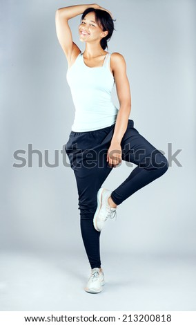 Fitness woman in sport style posing with toothy smile in studio, looking at camera. - stock photo