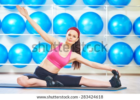 fitness woman instructor doing stretching pilates exercises split in sport club - stock photo