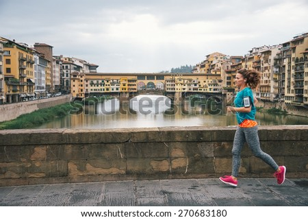Fitness woman jogging in front of ponte vecchio in florence, italy - stock photo