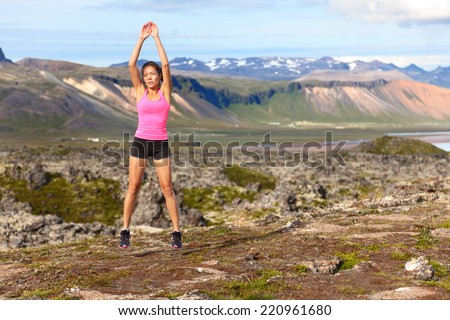 Fitness woman jumping exercising outdoors doing jump squats in amazing nature landscape. Fit female athlete cross-training outside. Image from Iceland. - stock photo