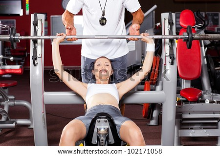 fitness woman lifting barbell in gym with personal trainer's help - stock photo