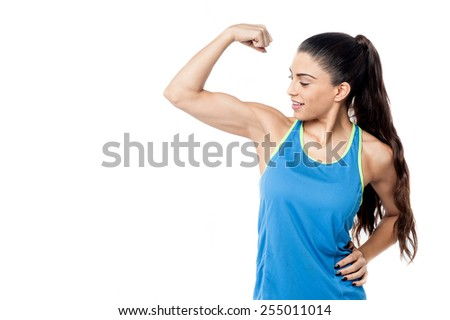Fitness woman looking at her biceps after exercise - stock photo