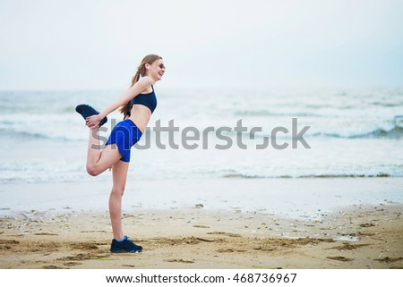 Fitness woman on beach doing stretching exercise after a workout. Jogger stretching muscles after run near sea or ocean. Fitness and healthy lifestyle concept