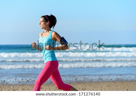 Fitness woman on running workout at the beach on summer. Sporty girl wearing earphones and sport armband for listening smartphone music. Female healthy athlete training outdoors on sea background. - stock photo