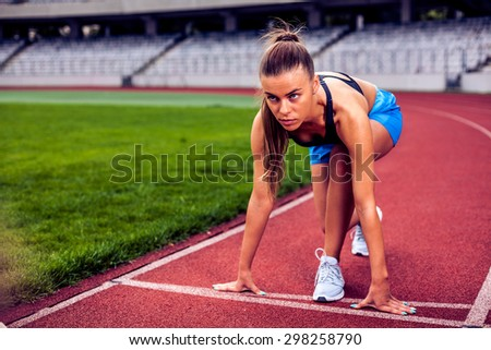 Fitness woman on stadium preparing for the start of the race - stock photo