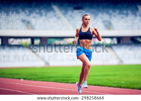 Fitness woman on stadium running - stock photo