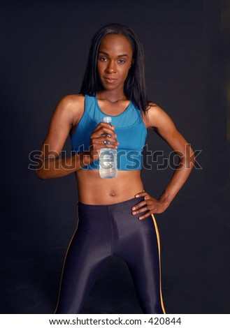 Fitness woman poses with water