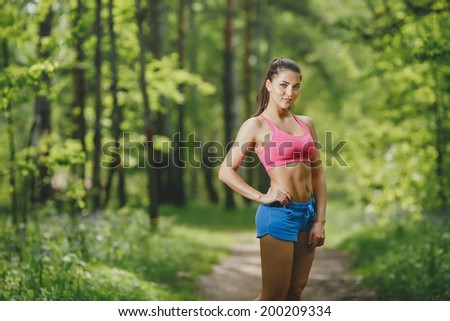 Fitness woman runner relaxing after forest running and working out outdoors in recreation park