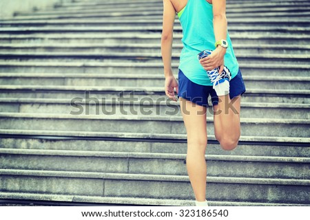 fitness woman runner stretching legs on stairs - stock photo