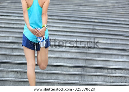fitness woman runner stretching legs on stairs