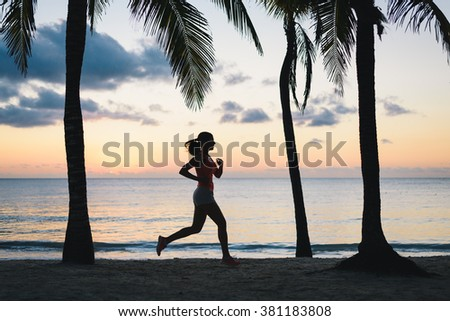 Fitness woman running at dusk on a tropical caribbean beach. Female athlete exercising during travel vacation at Riviera Maya, Mexico. - stock photo