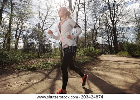 Fitness woman running in park on summer day. Caucasian female runner during outdoor workout. Fit female model jogging in forest. - stock photo
