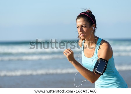 Fitness woman running on beach while listening music. Sporty girl wearing arm sport band for smartphone. - stock photo