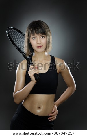 fitness woman shot in the studio low key lighting holding a tennis racket
