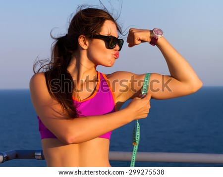 Fitness woman showing fresh energy flexing biceps muscles. Funny photo where girl what to kiss her biceps.Cheerfully smiling mixed race sporty woman demonstrating biceps with amazing sea background - stock photo