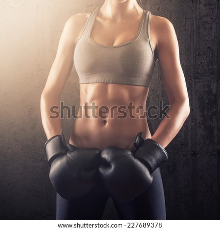 Fitness woman showing strong abs with boxing gloves on her hands - stock photo