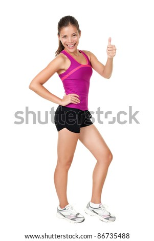 Fitness woman showing thumbs up success sign standing in running  outfit in full body isolated on white background. Healthy lifestyle concept of happy young mixed race Chinese Asian / Caucasian model.