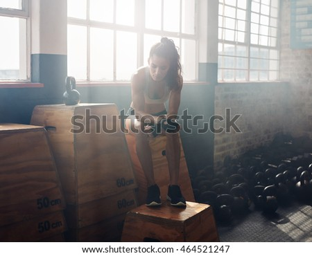 Fitness woman sitting on a box at gym after her workout. Female athlete taking break after exercising at gym.
