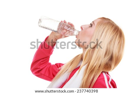 Fitness woman sport girl with white towel on her shoulders drinking water from bottle isolated on white. Studio shot. Training and workout.