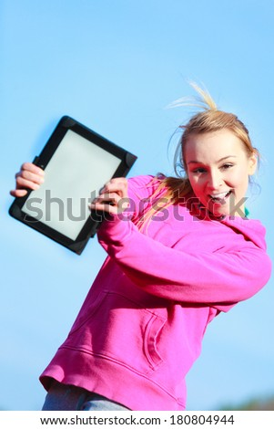 Fitness woman sport teenage girl in pink tracksuit showing blank copy space screen of tablet touchpad computer outdoor. Electronic technology. - stock photo