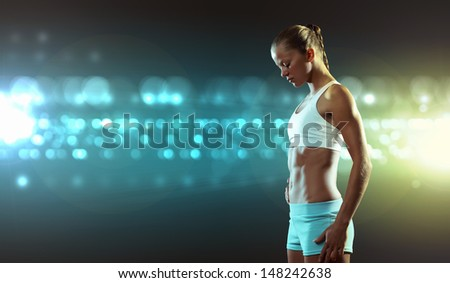 Fitness woman standing against color lights background - stock photo