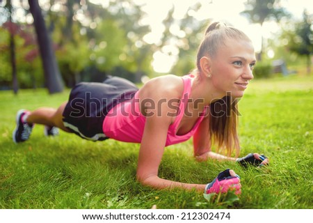 fitness woman stretching and working out in park, on grass - stock photo
