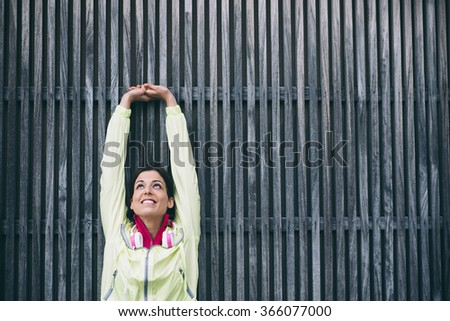 Fitness woman stretching arms and back against a wall. Female athlete working out and exercising outside. - stock photo