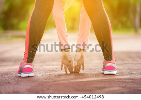 Fitness woman stretching her muscles before training, ready for jogging in summer park. Healthy lifestyle and sport concept