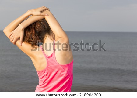 Fitness woman stretching her triceps on the beach - stock photo