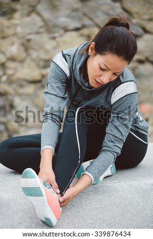 Fitness woman suffering painful ankle sprain injury after running or working out. - stock photo