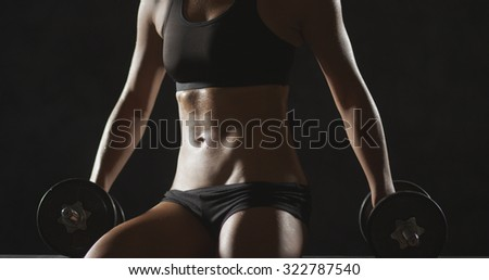 Fitness woman sweating after work out holding dumbbells - stock photo