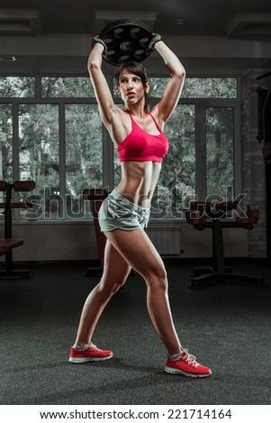 Fitness woman swinging kettle bell at gym. Young caucasian woman doing swing exercise with a kettlebell as a routine of a crossfit workout. - stock photo