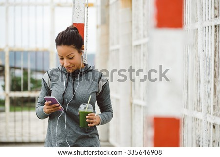 Fitness woman taking a workout rest for texting on her smartphone while drinking a nutritive detox smoothie and listening music. Healthy modern lifestyle and sport concept. - stock photo